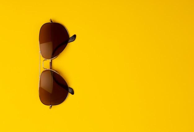 Okulary przeciwsłoneczni odizolowywający na żółtym tle z copyspace.