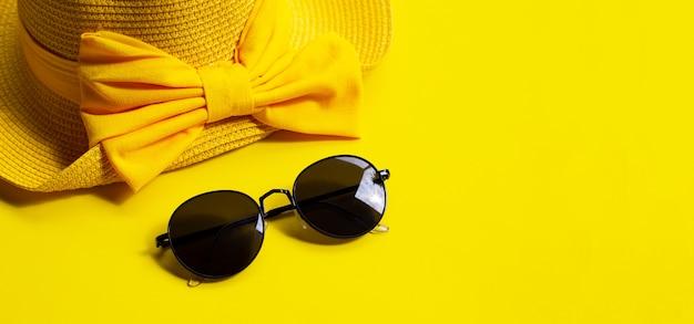 Okulary przeciwsłoneczni z lato kapeluszem na żółtym tle. ciesz się wakacyjną koncepcją.