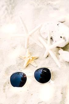 Okulary przeciwsłoneczni z rozgwiazdą i koralem na plaży