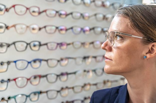 Okulary są wybierane i testowane przez kobietę w sklepie z optyką