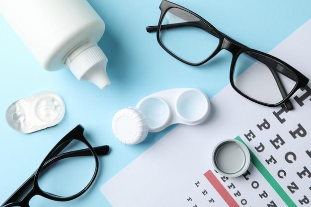 Okulary, soczewki kontaktowe i tabela testowa oka na niebieskiej powierzchni, widok z góry