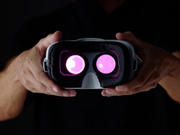 Okulary vr w rękach człowieka. urządzenie do gier gogle wirtualnej rzeczywistości i ramię. ciemne tło