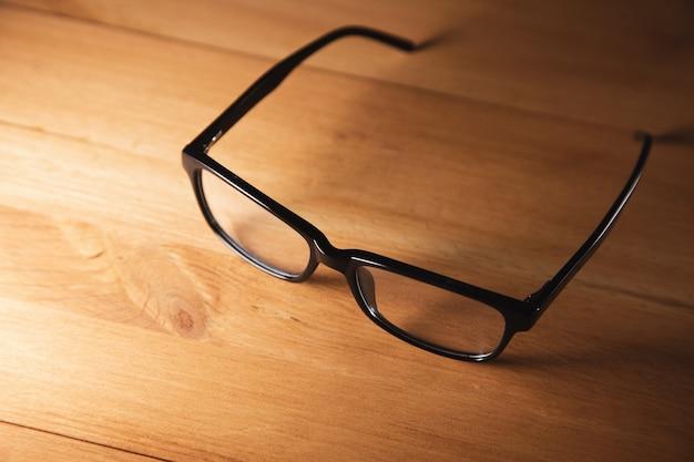 Okulary w czarnej oprawce na drewnianym biurku