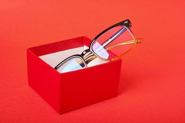 Okulary w czerwonym pudełku na czerwonym tle miejsca kopiowania