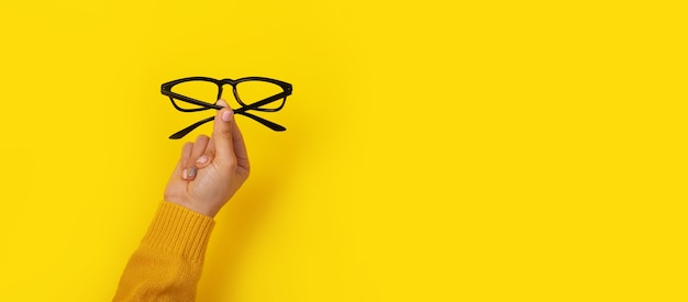 Okulary w dłoni na żółtym tle, szablon przestrzeni kopii, baner.