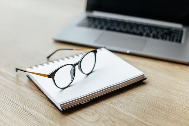 Okulary w miejscu pracy w biurze w pobliżu laptopa i notatnika. godziny pracy