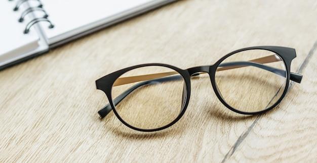 Okulary w miejscu pracy w biurze w pobliżu notatnika. godziny pracy