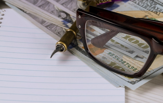 Okulary w ramce są na dolarach z notatnikiem i piórem