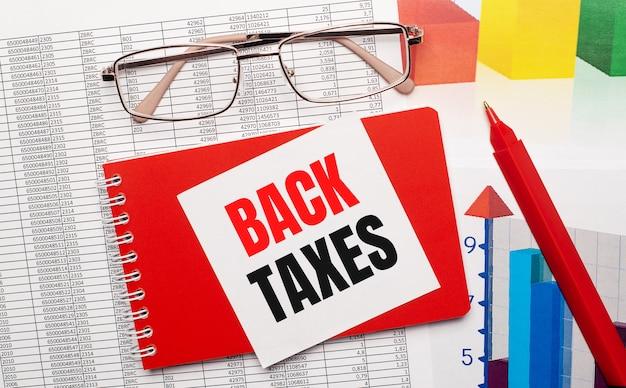 Okulary w złotych oprawkach, czerwony długopis, kolorowe tabele i czerwony notes z białą kartą z napisem back taxes na pulpicie