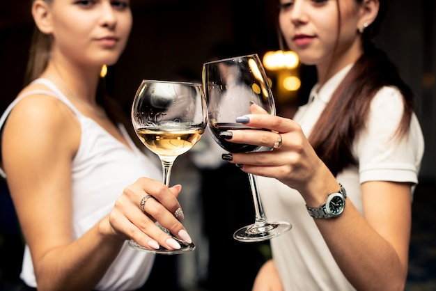 Okulary z czerwonymi i białymi winami w rękach pięknych dziewczyn ubranych w białe bluzki