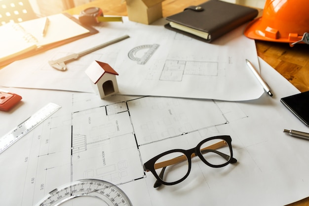 Okulary z modelem domu architekta i itp. na biurku architekta.