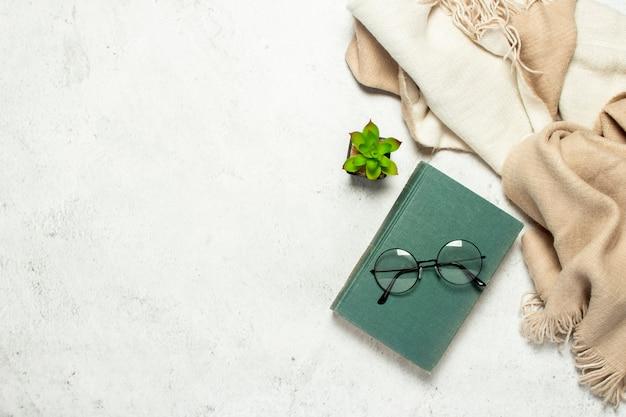 Okulary z okrągłymi okularami leżą na książce, wełniany szalik i kwiat pokoju na białym tle światła.