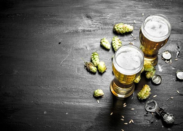 Okulary z piwem i zielonym chmielem na czarnej tablicy.