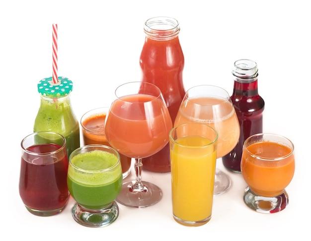 Okulary z różnymi świeżymi sokami warzywnymi na białym tle