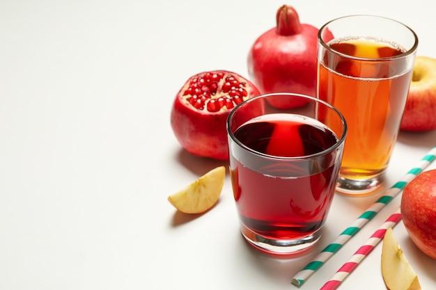 Okulary z sokami jabłkowymi i granatowymi na białym tle