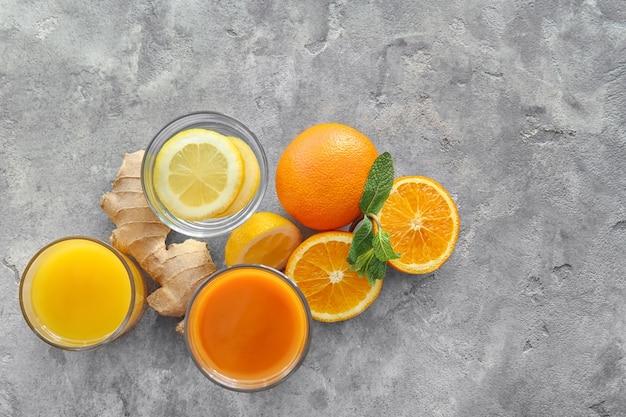 Okulary z sokiem i owocami cytrusowymi na szarym tle. koncepcja zdrowej żywności