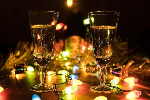 Okulary z szampanem na tle girlandy. walentynki tło. obchody bożego narodzenia i nowego roku zakochanych par