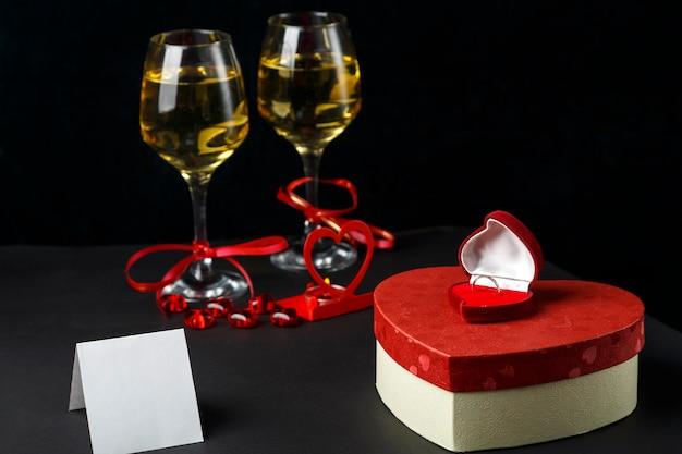 Okulary z szampanem związany wstążką na czarnym tle pudełka z prezentami i kartami. poziome zdjęcie