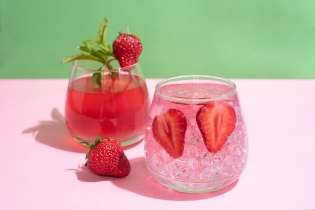 Okulary z wodą funkcjonalną, lemoniada truskawkowa z kostkami lodu na zielonym i różowym tle, koncepcja letnich napojów, z bliska.