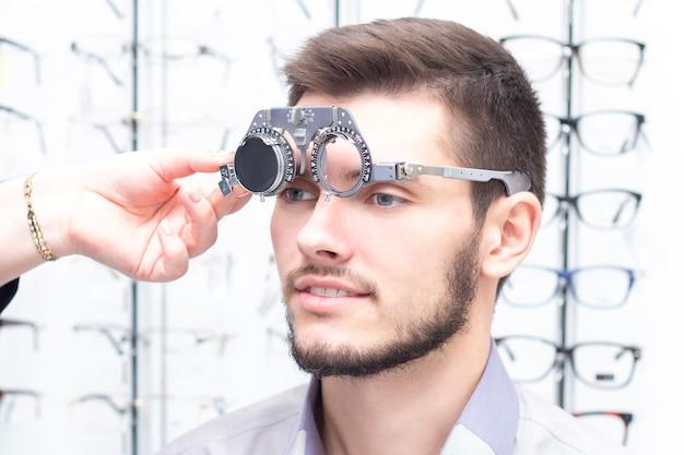 Okulista bada młodego człowieka w klinice. konsultacja okulisty. wyposażenie medyczne. correometry