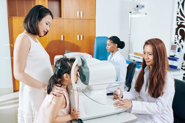 Okulista dziecięcy sprawdzający dno oka małej dziewczynki za pomocą aparatu bez rozszerzenia źrenic w klinice