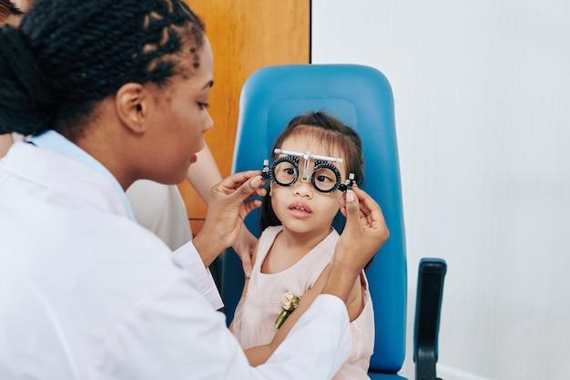 Okulista dziecięcy sprawdzający wzrok i dobierający soczewki korekcyjne dla małej dziewczynki