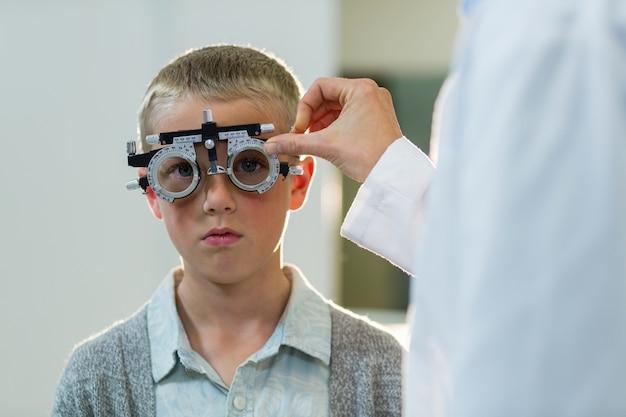 Okulista egzamininuje młodego pacjenta z phoropter