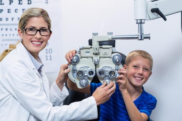 Okulista i młody pacjent uśmiechając się podczas badania wzroku