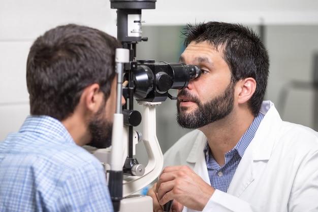 Okulista lekarz mężczyzna sprawdza wzrok widzenia przystojnego młodego człowieka w nowoczesnej klinice