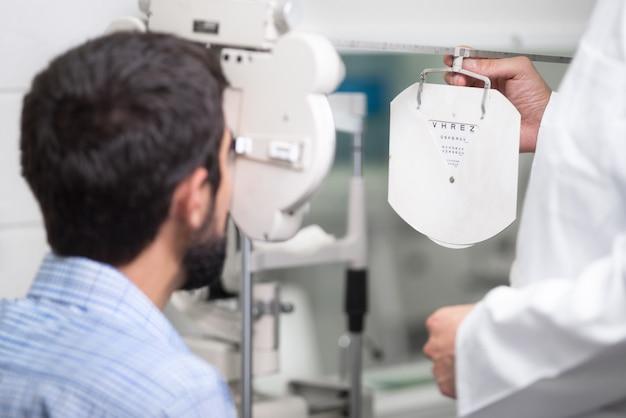 Okulista lekarz mężczyzna sprawdza wzrok widzenia przystojnego młodego człowieka w nowoczesnej klinice.