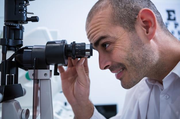 Okulista patrząc przez biomikroskop