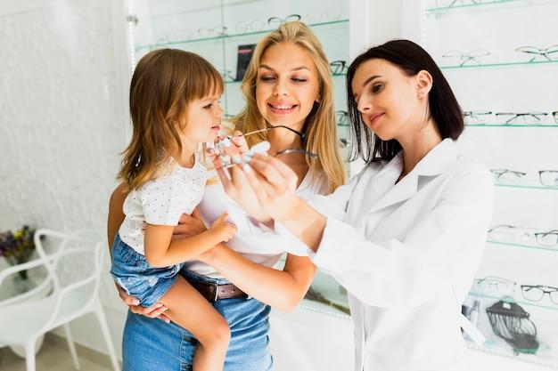 Okulista pokazuje małej dziewczynki szkieł ramę