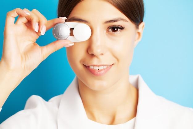 Okulista trzyma pojemnik z soczewkami kontaktowymi w pobliżu oczu