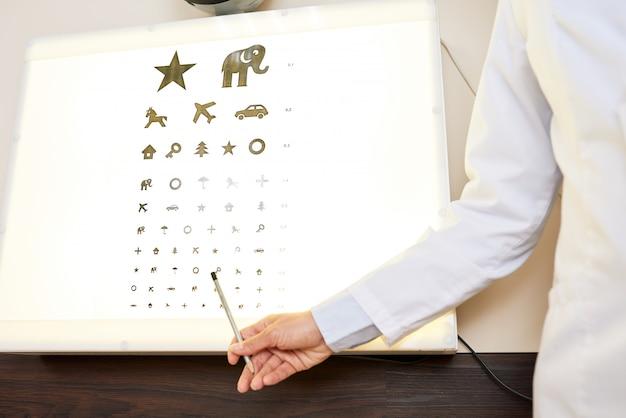 Okulista, wskazując na wykres oka