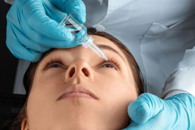 Okulista wstrzykuje krople do oczu pacjentów w klinice okulistycznej. zdrowie, wzrok, choroby oczu.