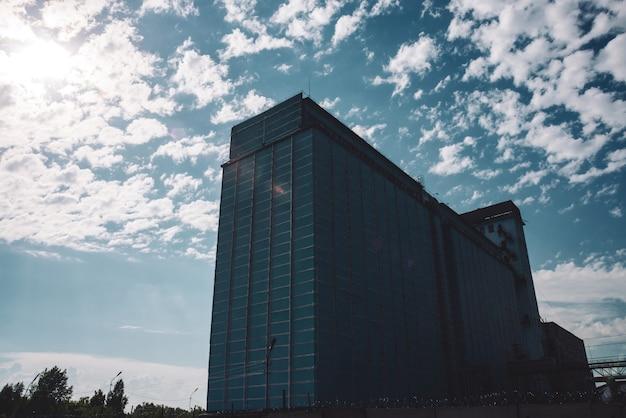Olbrzymi wielopiętrowy budynek produkcyjny za płotem z drutem kolczastym. malownicza stara odnowiona działająca fabryka. starzejący się obiekt przemysłowy. duży wieżowiec produkcyjny. zbliżenie obszaru przemysłowego.