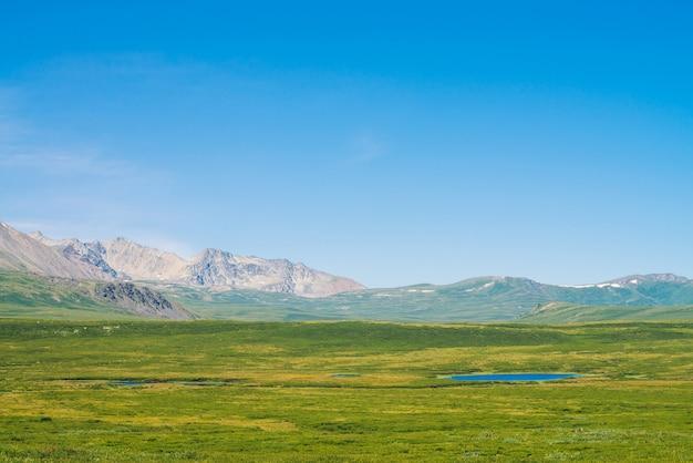 Olbrzymie góry ze śniegiem nad zieloną doliną pod jasnym niebieskim niebem. łąka z bogatą roślinnością i jeziorami wyżynnymi w słońcu. niesamowity słoneczny górski krajobraz majestatycznej przyrody.