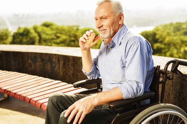 Old man eating burger. rehabilitacja na świeżym powietrzu.