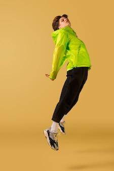 Oldschoolowy młody mężczyzna tańczy na białym tle na żółtym tle