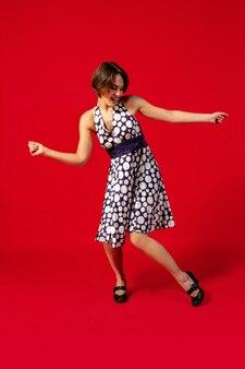 Oldschoolowy styl młodej kobiety tańczy na białym tle na czerwonym tle