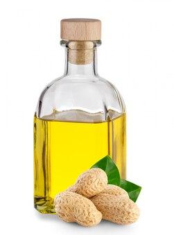 Olej arachidowy w przezroczystej butelce i orzeszki ziemne z liśćmi