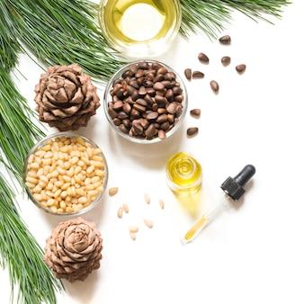 Olej cedrowy, gałęzie i stożek cedrowy na białym tle. skopiuj miejsce. piękna i zdrowa koncepcja.