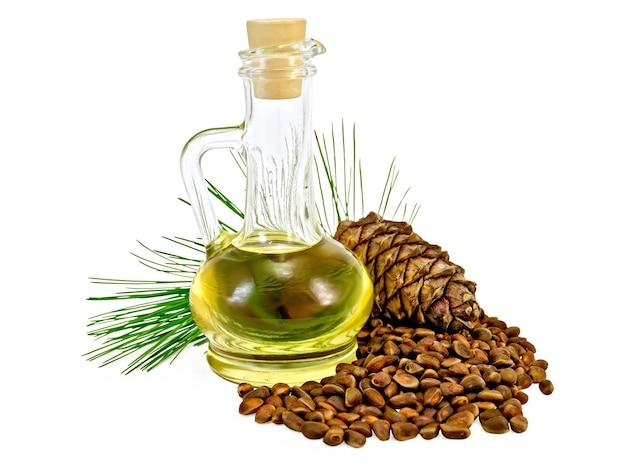 Olej cedrowy w szklanej butelce, gałązka cedru z szyszkami cedrowymi, orzechy cedrowe na białym tle