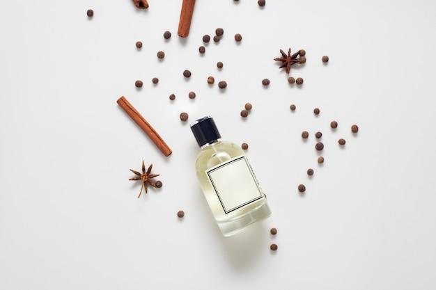 Olej cynamonowy, ozdobiony laskami cynamonu i przyprawami z gwiazdami, na białej ścianie, widok z góry. koncepcja pielęgnacji ciała, naturalne oleje.