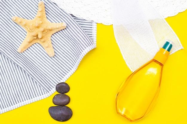 Olej do garbowania na żółtym stole. gładka opalenizna idealne ciało. piękno . ochrona przed słońcem. odpoczynek na plaży. artykuł o środkach do opalania. letnie wakacje. kamienie morskie zen