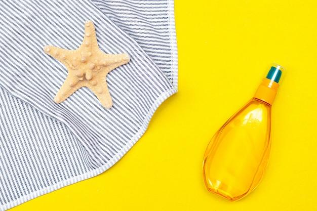 Olej do garbowania na żółtym stole. gładka opalenizna idealne ciało. piękno . ochrona przed słońcem.