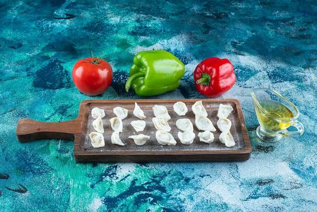 Olej i warzywa obok tureckich ravioli na desce, na niebieskim stole.