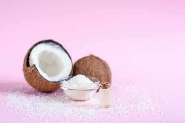 Olej kokosowy do pielęgnacji ciała w koncepcji organicznych kosmetyków na różowym tle.