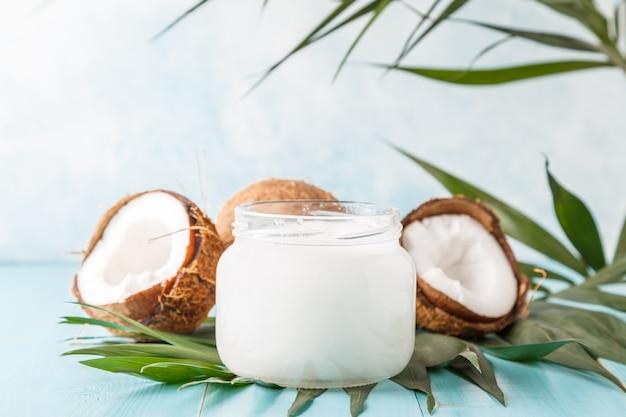 Olej kokosowy i orzechy kokosowe na jasnym, pastelowym tle