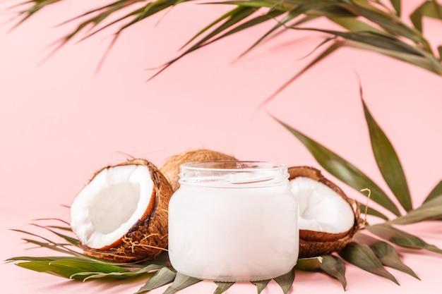 Olej kokosowy i orzechy kokosowe na tle z tropikalnymi liśćmi